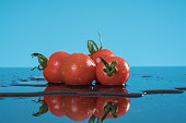 Bunch of fresh tomatoes on blue background