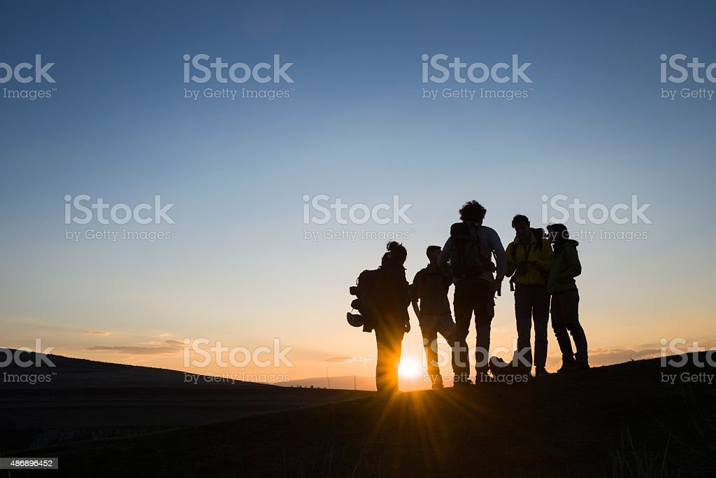Bunch of friends with backpacks at sunrise stock photo