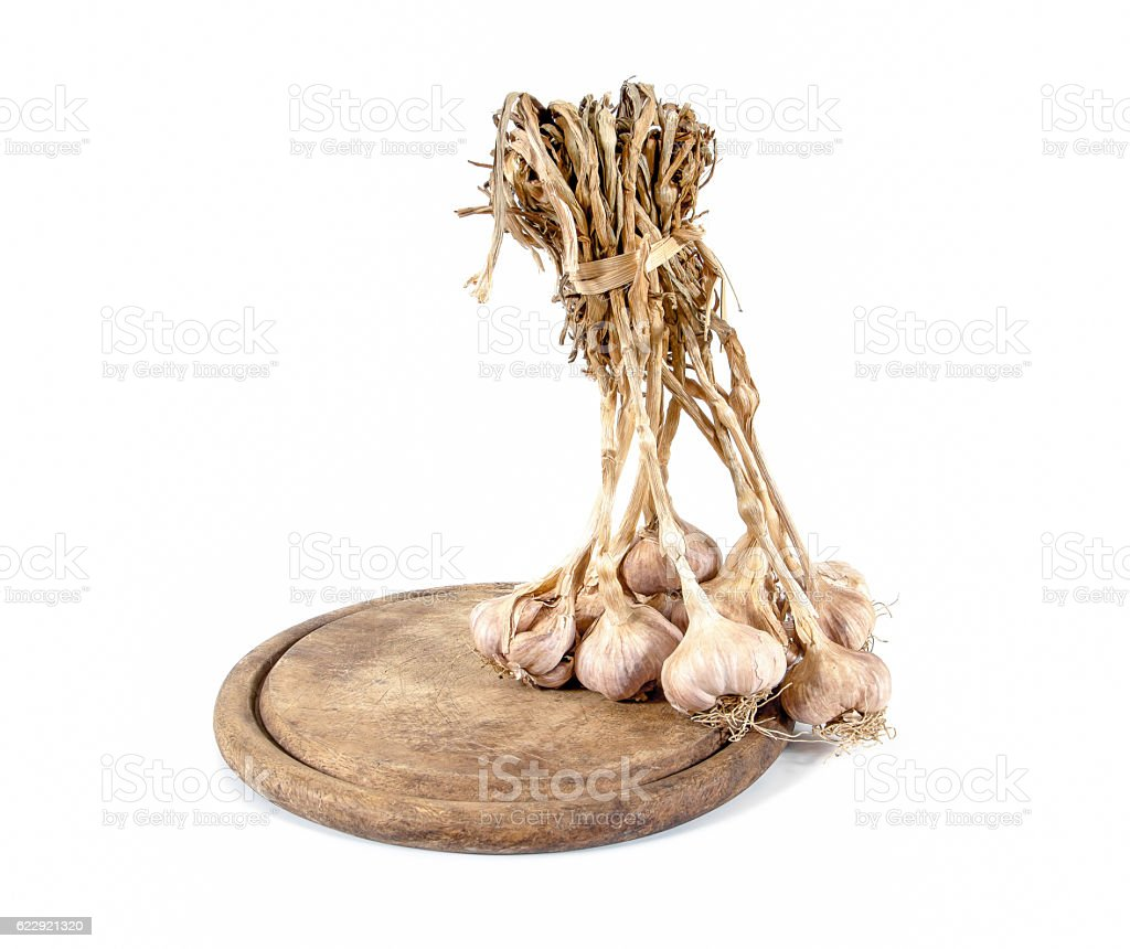 Bunch of garlic bulbs on round wooden chopping board stock photo