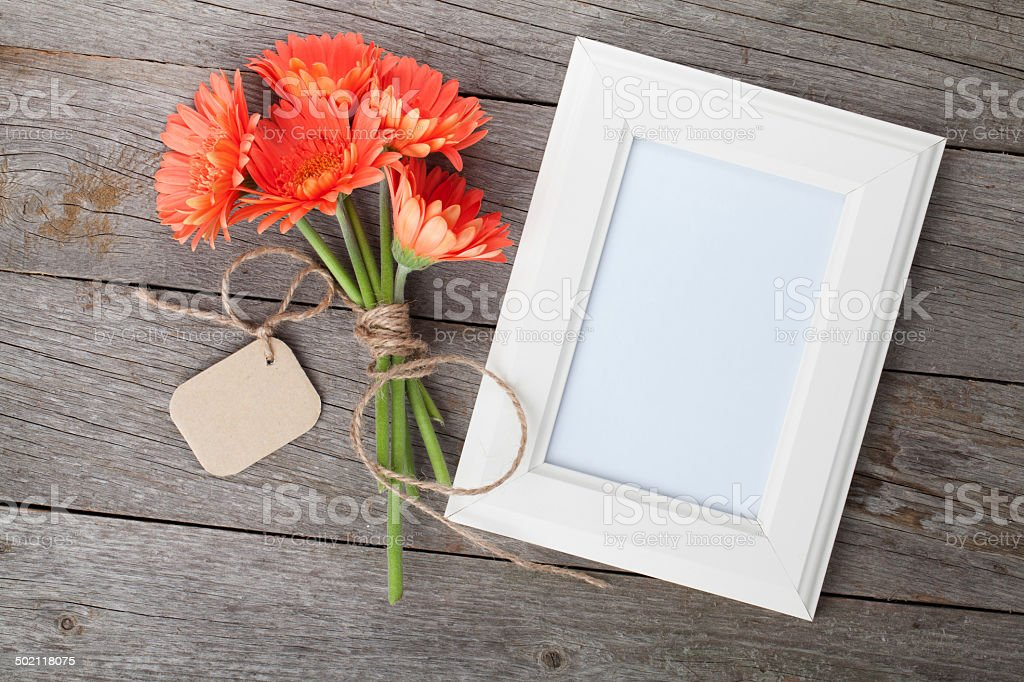 Bunch of gerbera flowers and photo frame stock photo