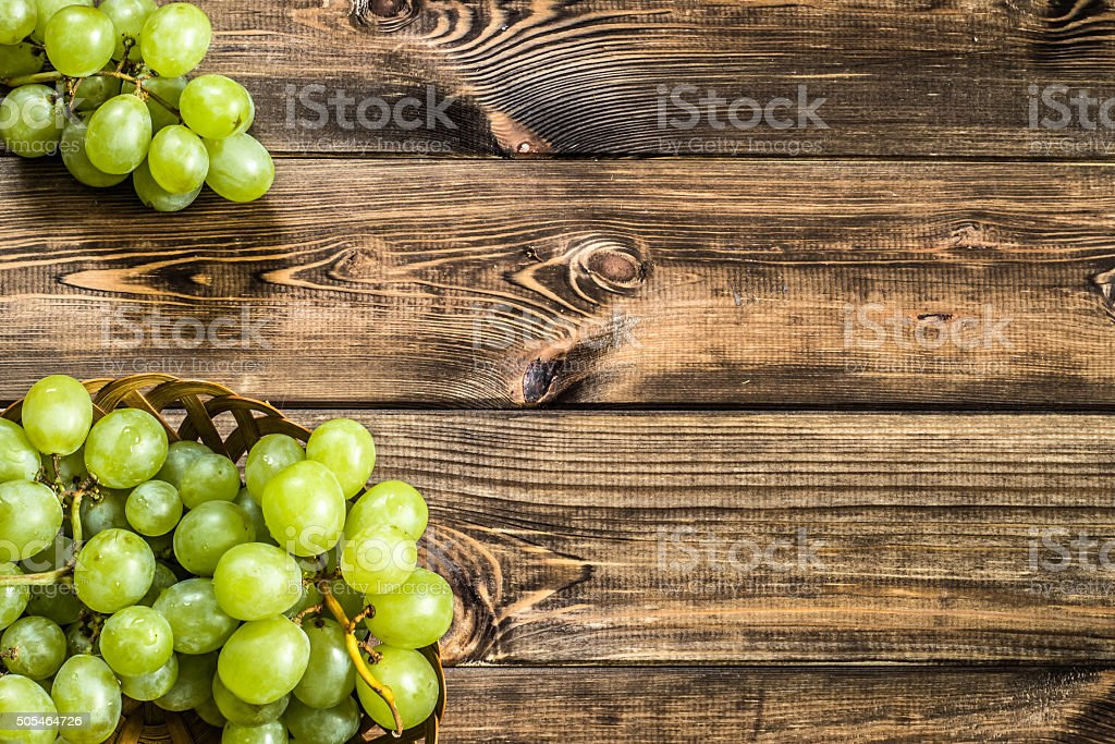 Bunch of grapes fruits in the basket on wooden background. stock photo