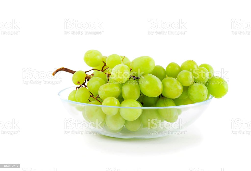 Bunch of grapes in a glass  bowl on white stock photo