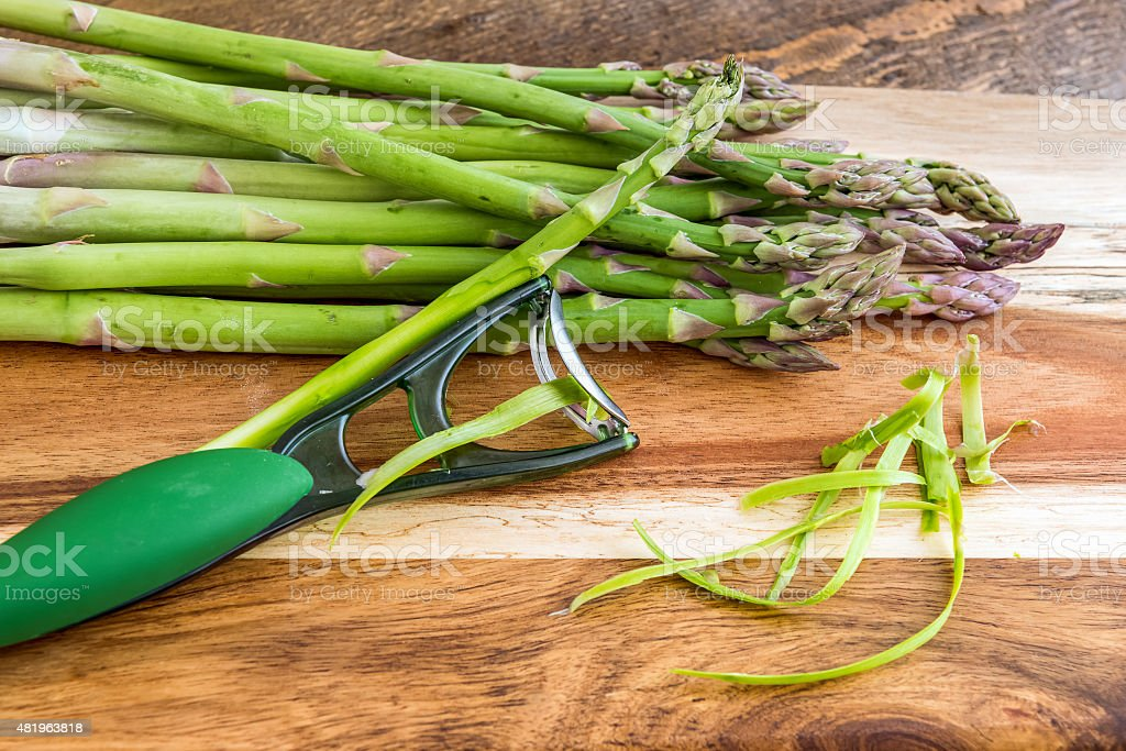Bunch of green asparagus with peeler on wooden background stock photo