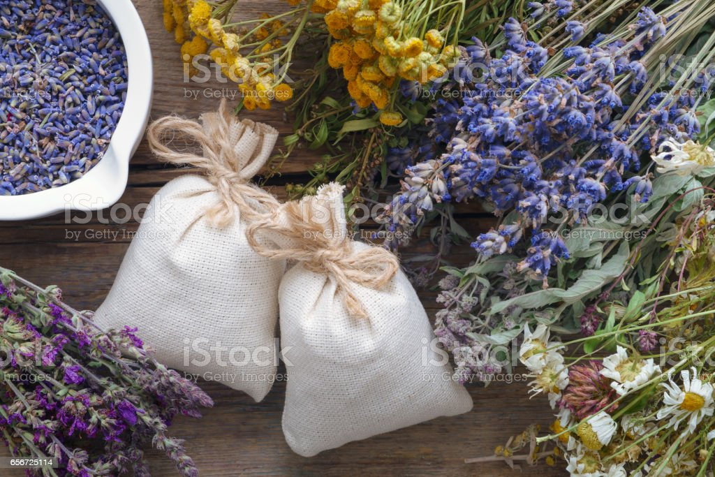 Bunch of healing herbs, mortar and sachet on wooden table. stock photo