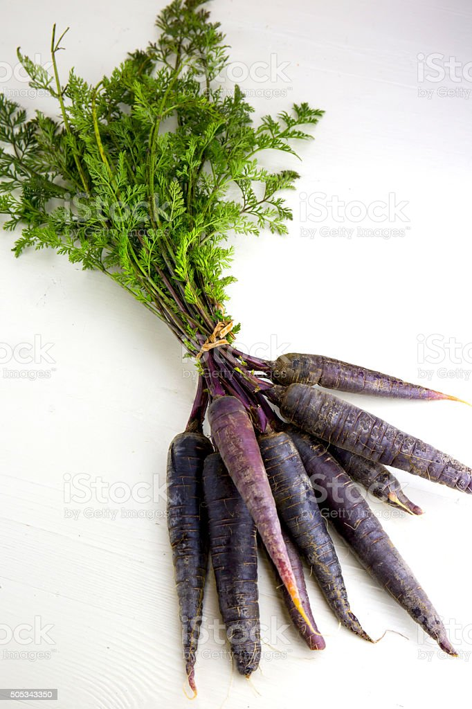 Bunch of heirloom purple carrots, over white and wooden backgrou stock photo