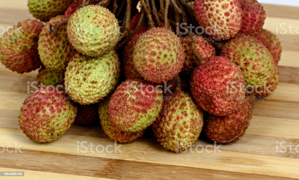 Bunch of lychee on old wooden cutting board stock photo