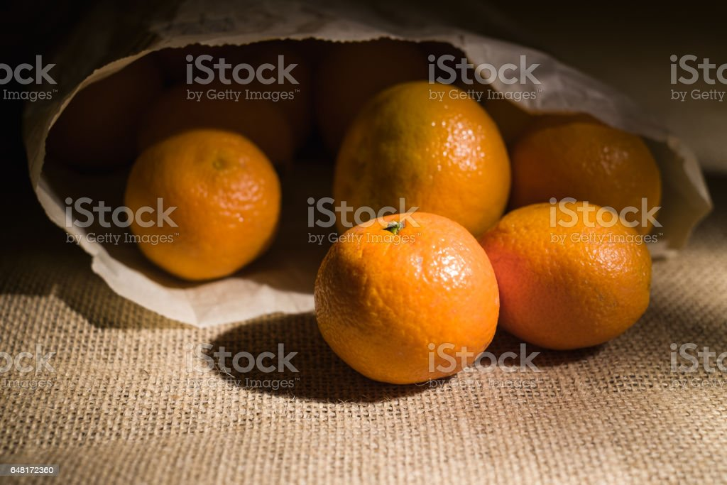 bunch of mandarines in paper bag on burlap surface spot lighted on dark background stock photo