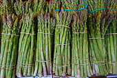 Bunch of mature asparagus standing on a greengrocer's shelf