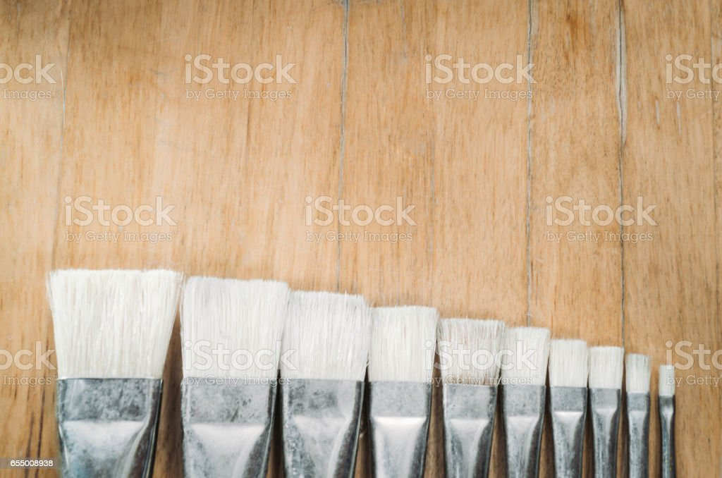 Bunch of old artist paintbrushes on wooden rustic table with space for text stock photo