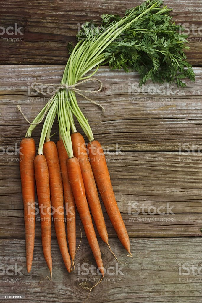 A bunch of organic carrots on a wooden surface  royalty-free stock photo