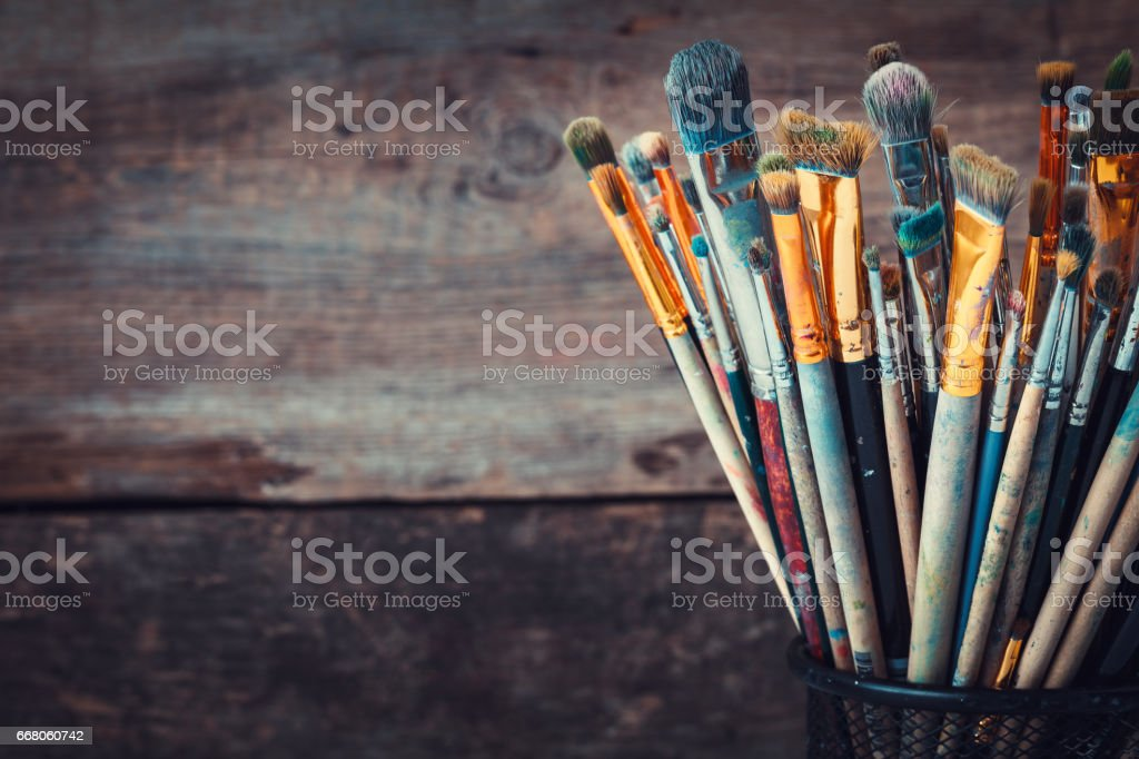 Bunch of paint brushes in a artist studio. Copy space for text. Retro toned photo. stock photo
