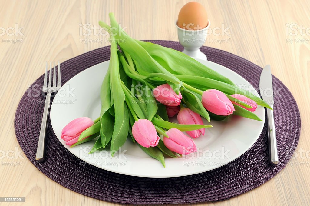 Bunch of pink tulips on plate with knife and fork royalty-free stock photo