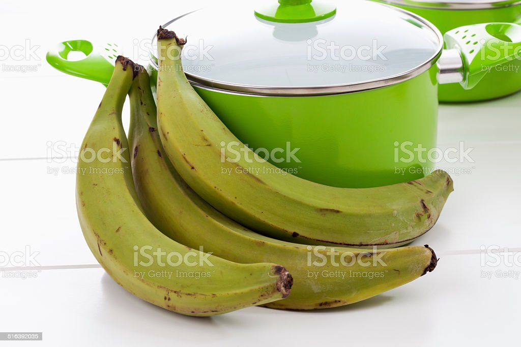 Bunch of plantains and green pot on white background stock photo