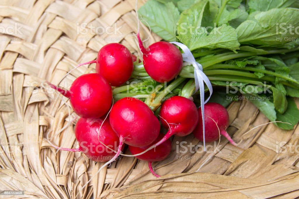 Bunch of radishes with leaves on wicker table stock photo
