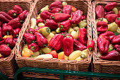 Bunch of red and yellow paprika peppers in wicker boxes
