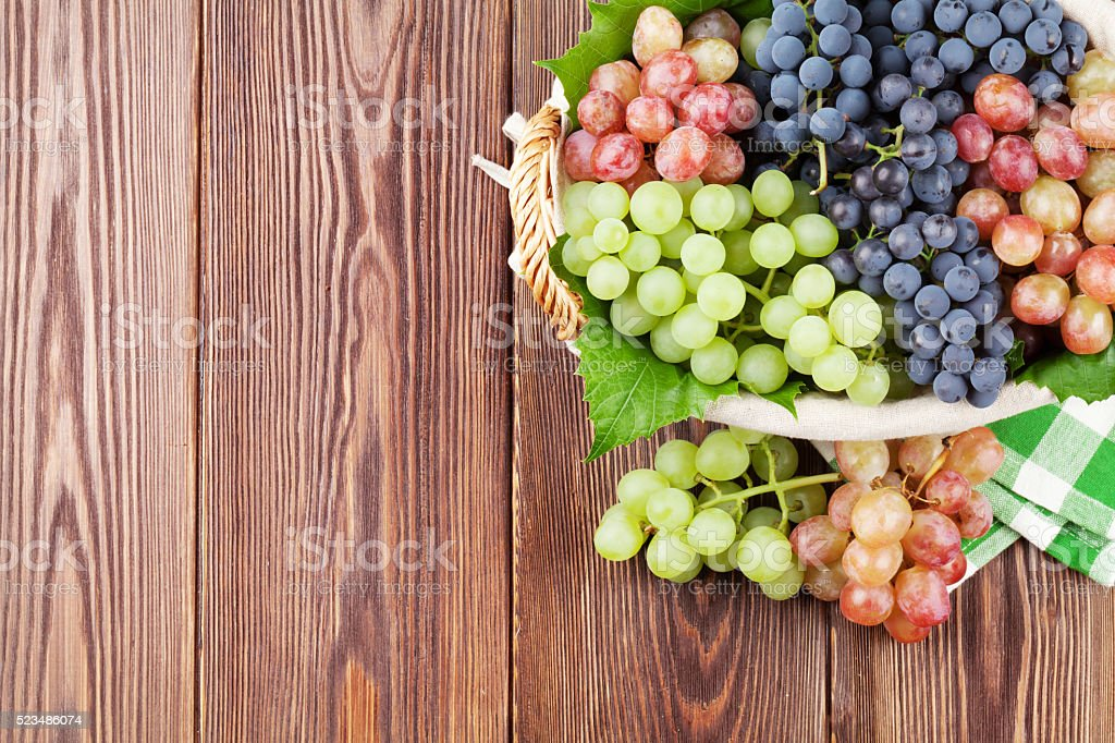 Bunch of red, purple and white grapes in basket stock photo