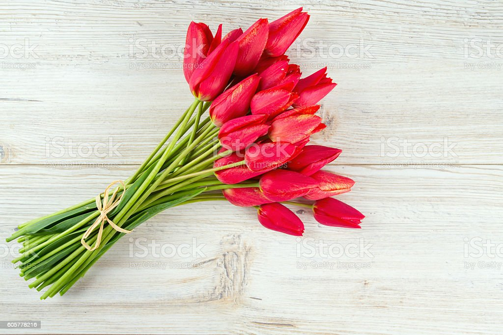 bunch of red tulips on wooden surface stock photo