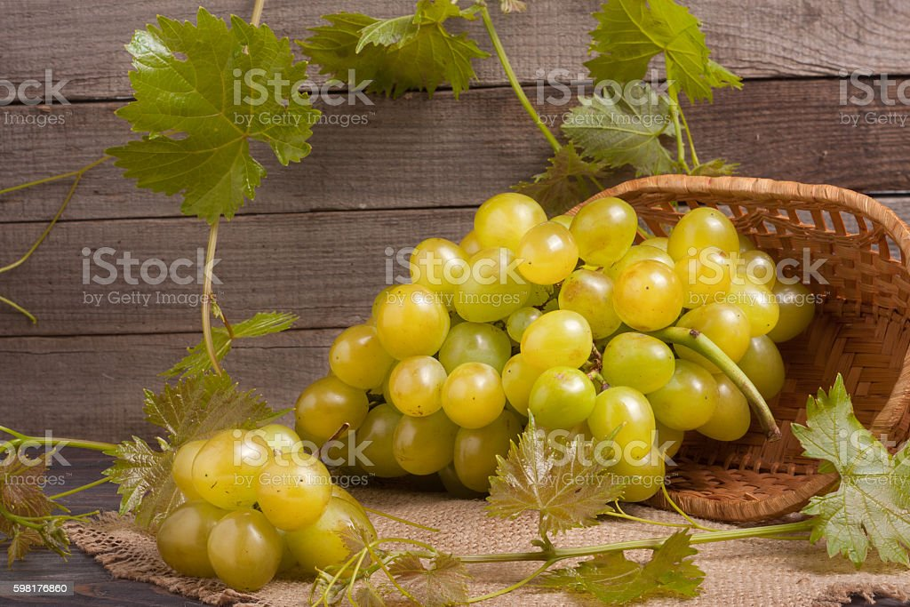 bunch of ripe green grapes on a wooden table with stock photo