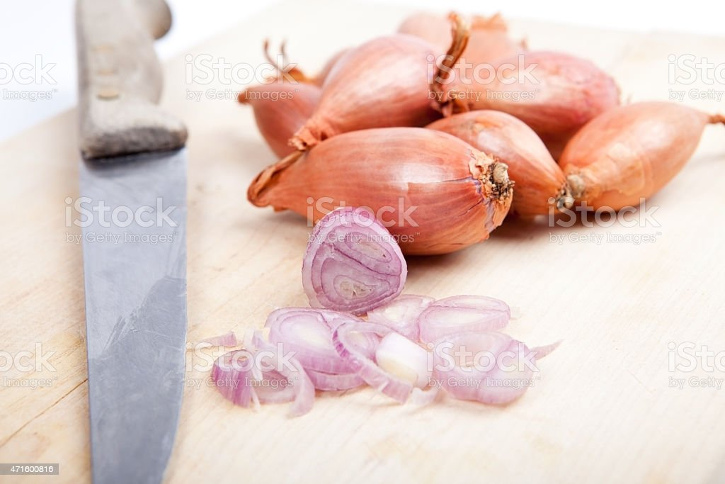 bunch of shallots and old knife on wooden board stock photo