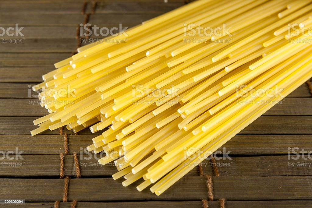 Bunch of spaghetti on wooden table background stock photo