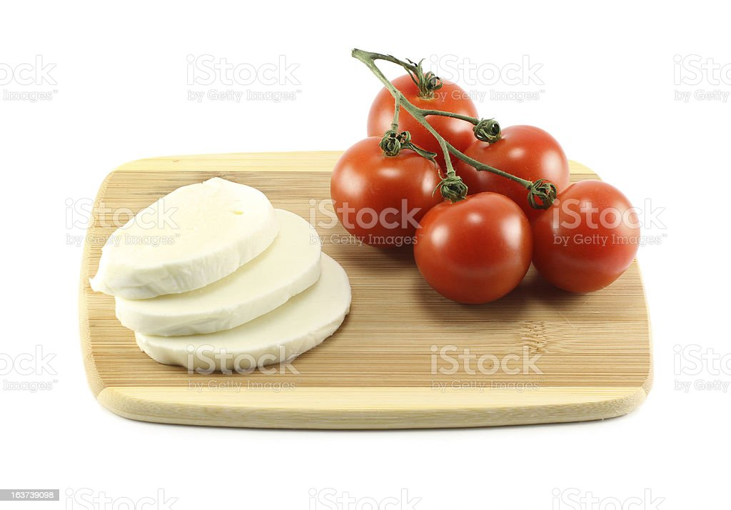 Bunch Of Tomatoes And Mozzarella Cheese On A Cutting Board royalty-free stock photo