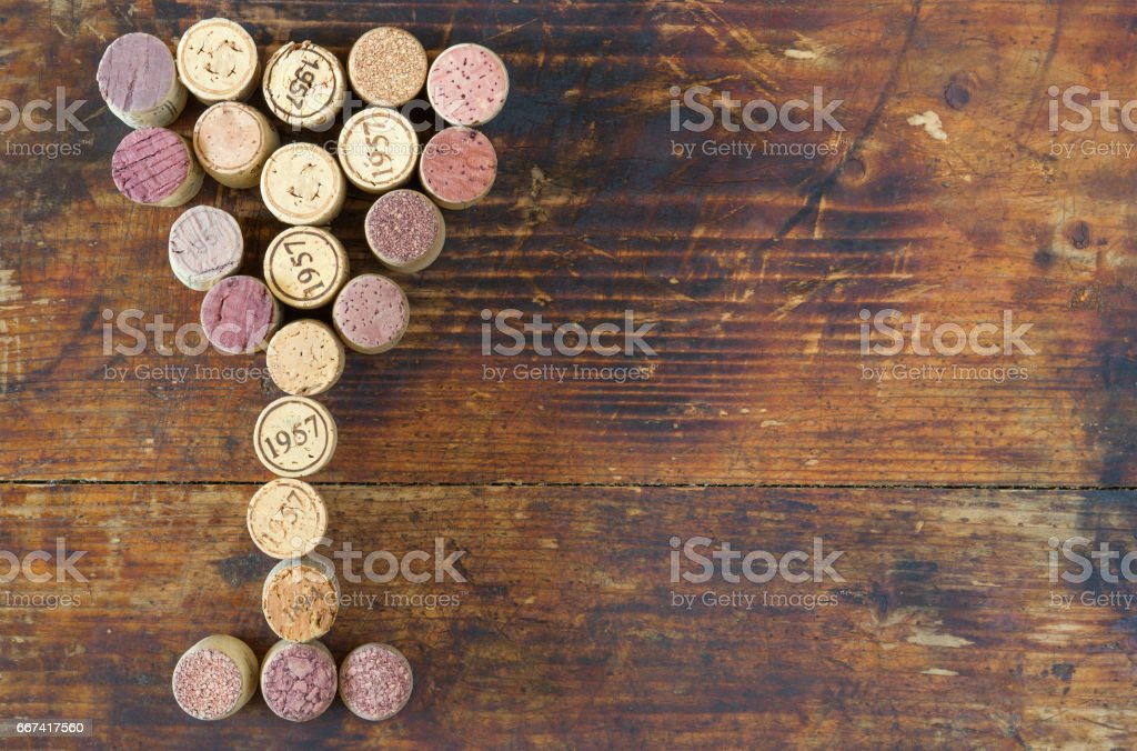 Bunch of used wine cork in shape of wine glass on old vintage cutting board. stock photo