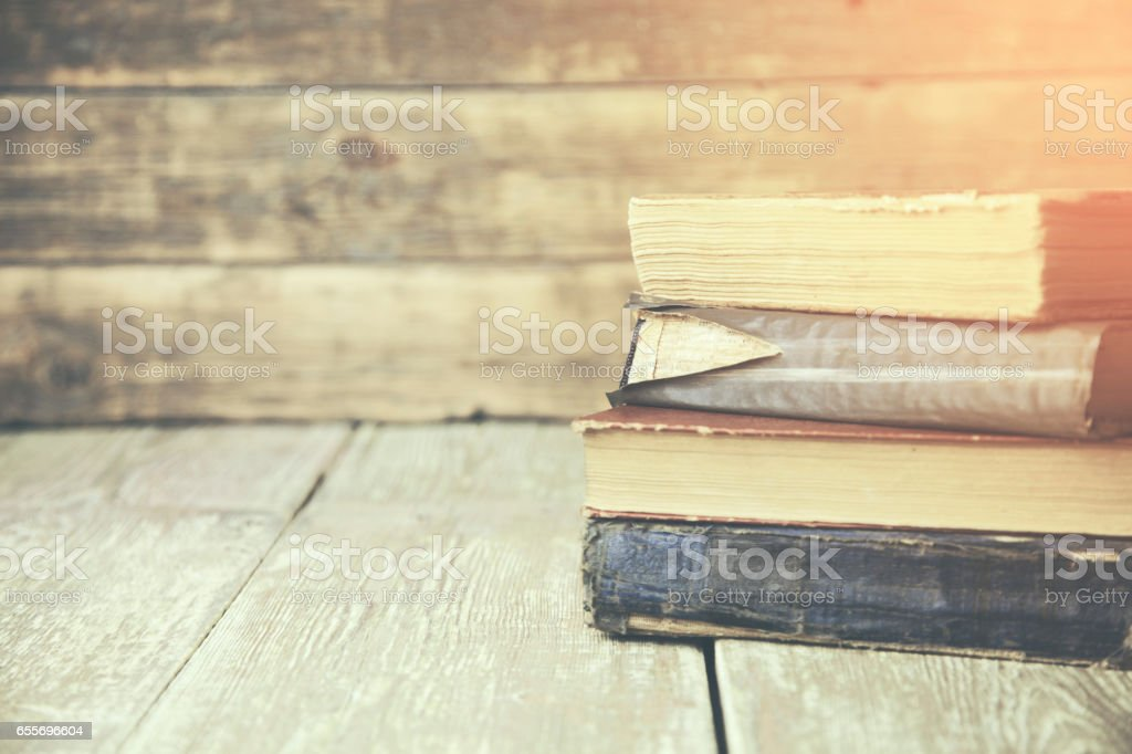 Bunch of vintage books on wooden table stock photo