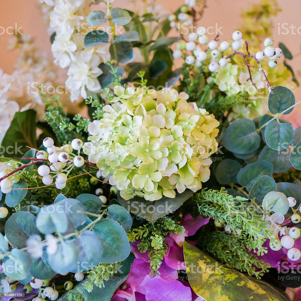 bunch of white flowers, green leaf in glass vase. stock photo