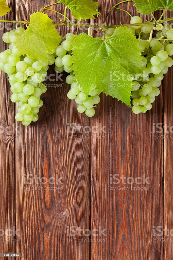 Bunch of white grapes with leaves on wood stock photo
