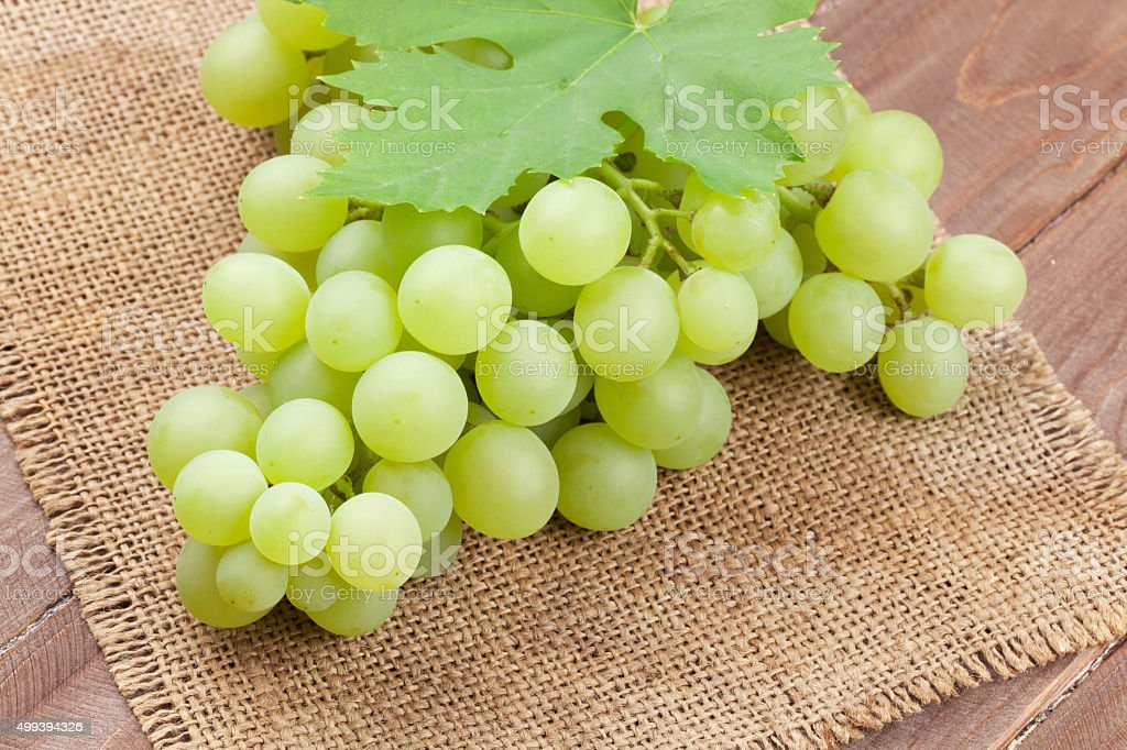 Bunch of white grapes with leaves over burlap stock photo