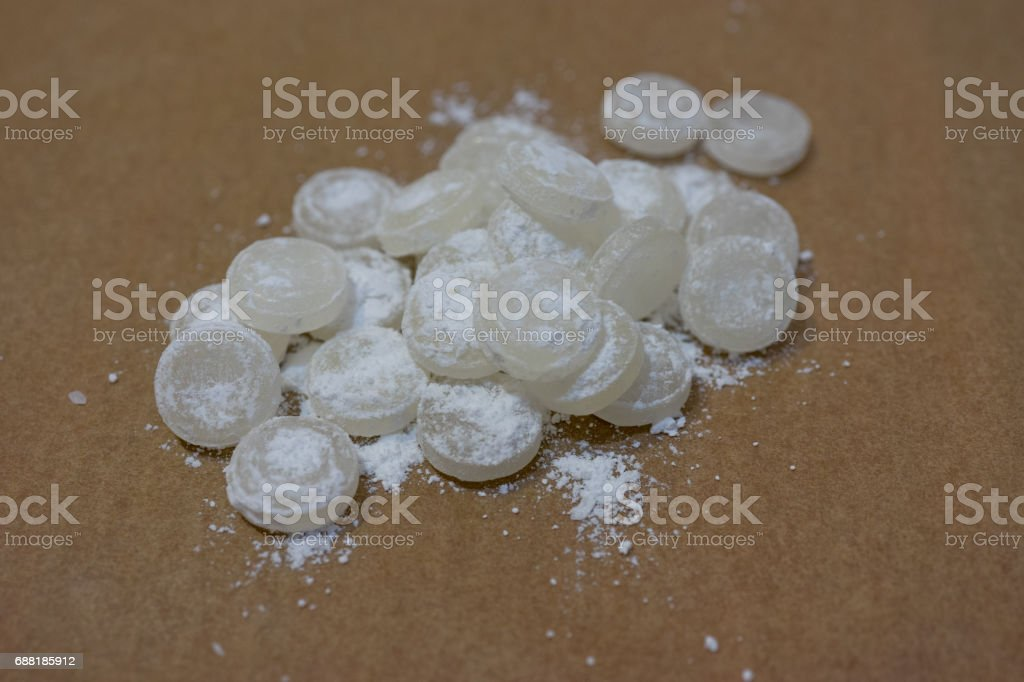 Bunch of white mint candies in powdered sugar on a thin sheet of parchment stock photo