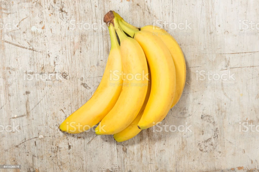 Bunch of Yellow Bananas on a Wooden Background stock photo