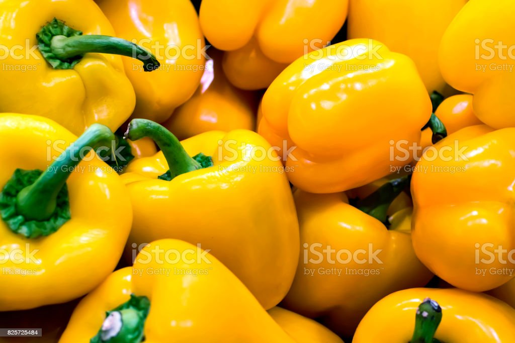 Bunch of yellow peppers in a greengrocery stock photo