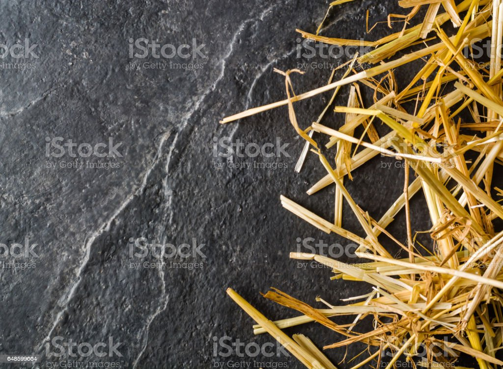 A bunch of yellow straw on the black background of an empty slab of slate. stock photo