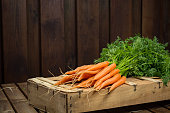 Bunch on fresh orange carrots on wooden box