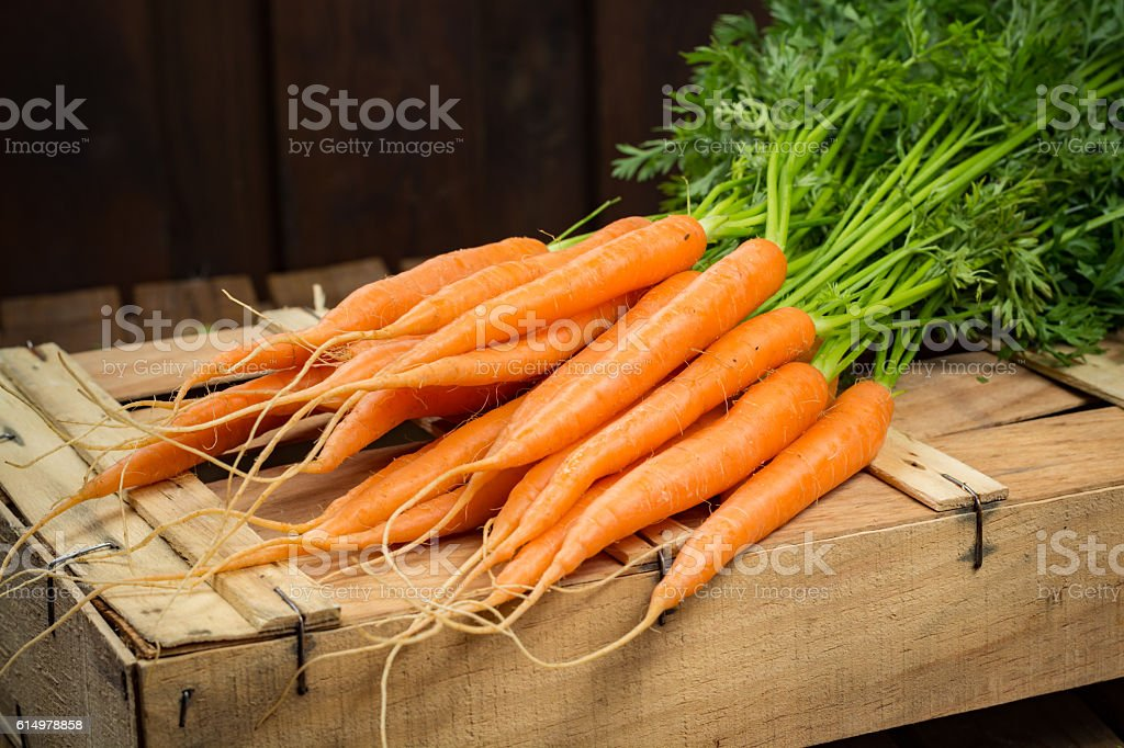 Bunch on fresh orange carrots on wooden box stock photo