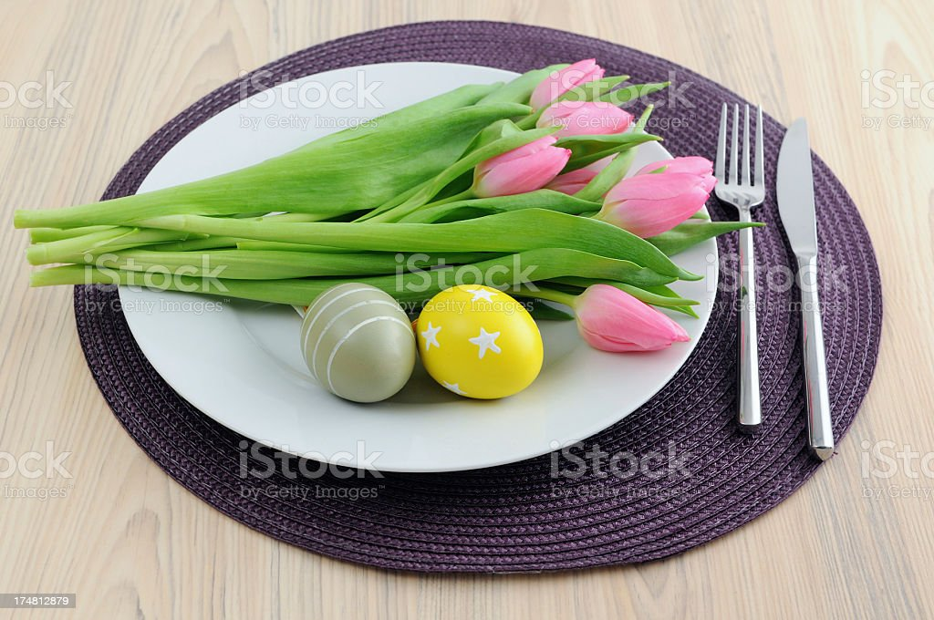 Bunch pink tulips and easter eggs on plate stock photo