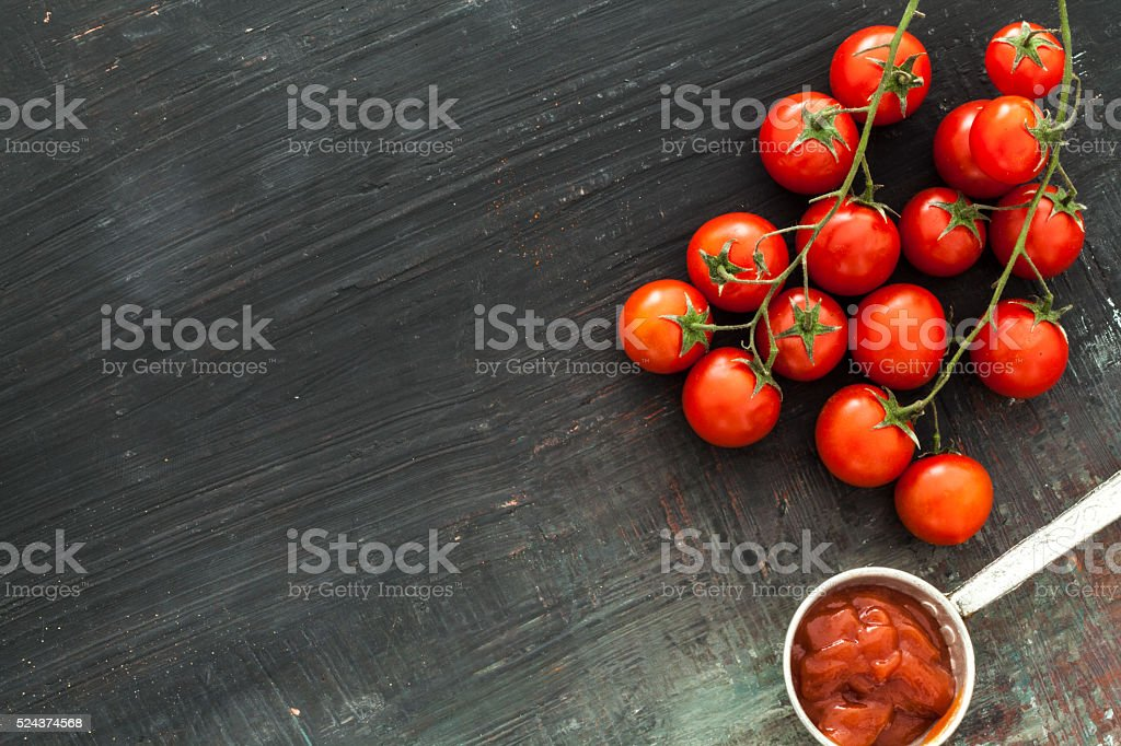 Bunch tomatoes and sauce on wooden background stock photo