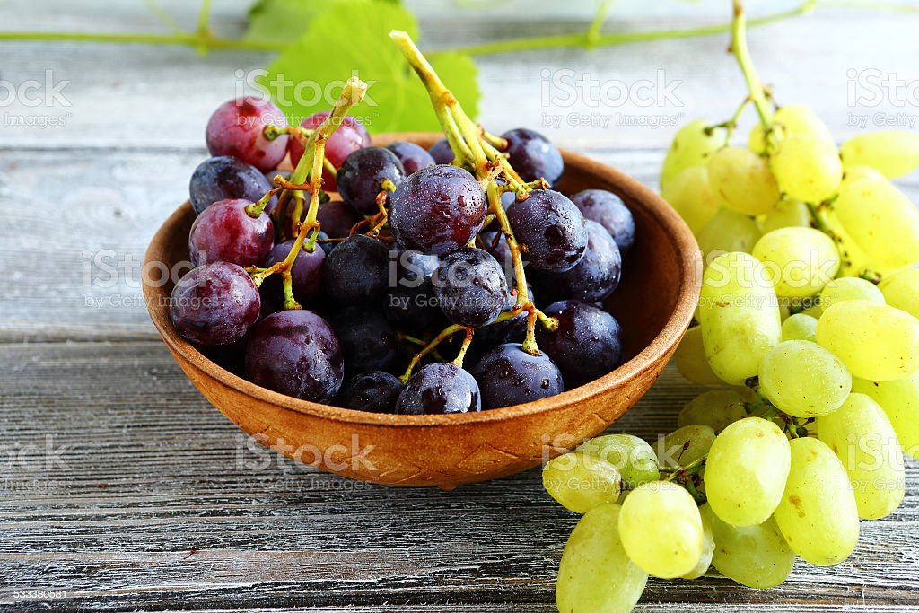 Bunches of grapes in bowl on wooden boards stock photo
