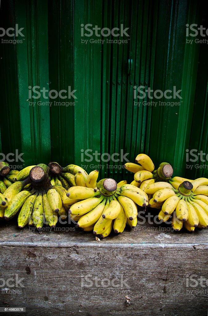 Bunches of Ripe Bananas on a Stone Step at Market stock photo