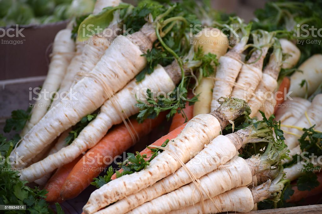 Bunches of root vegetables on the market stall stock photo