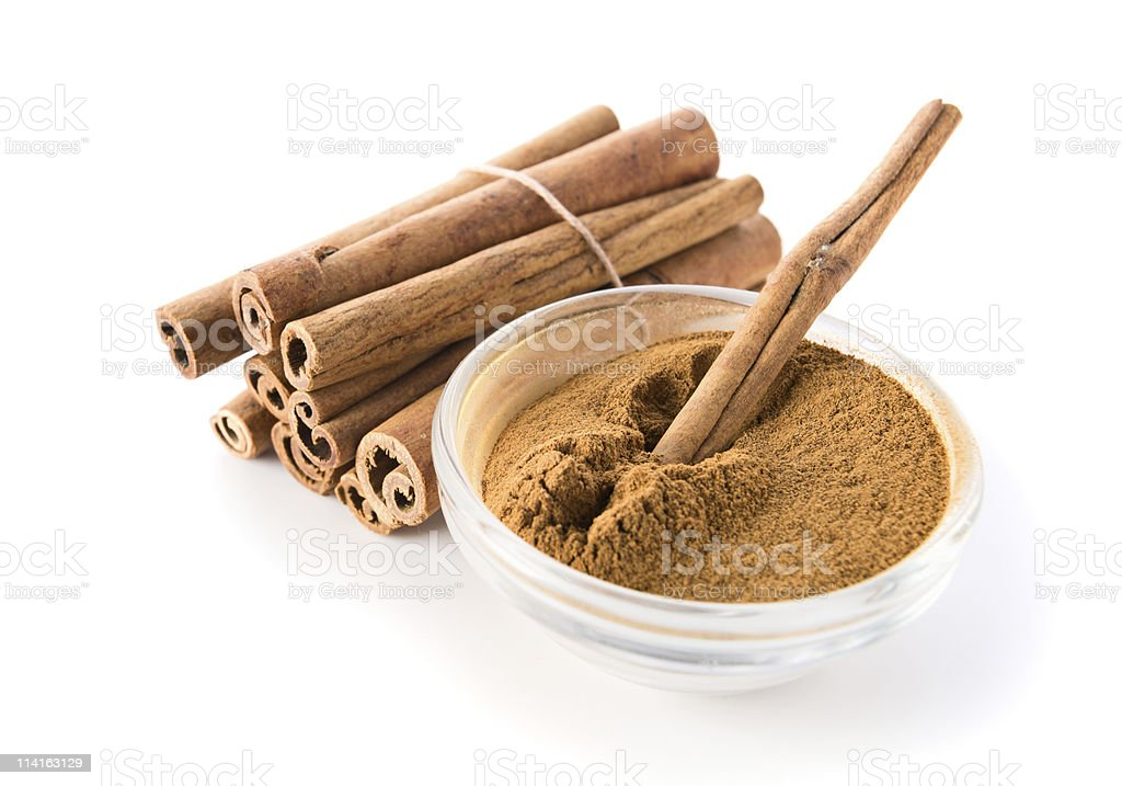 Bundle of cinnamon sticks and bowl of ground cinnamon stock photo