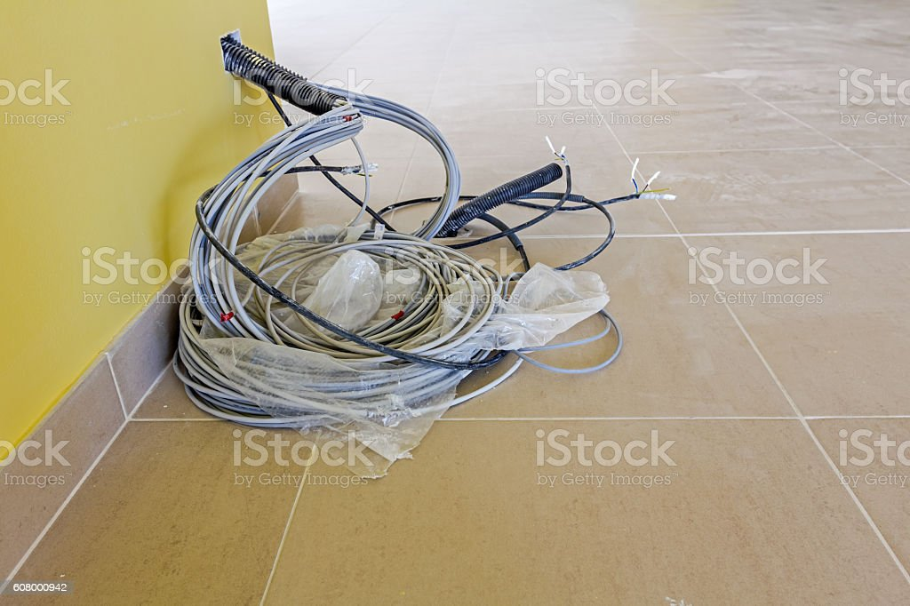 Bundle of communication cables are hanging from the wall stock photo