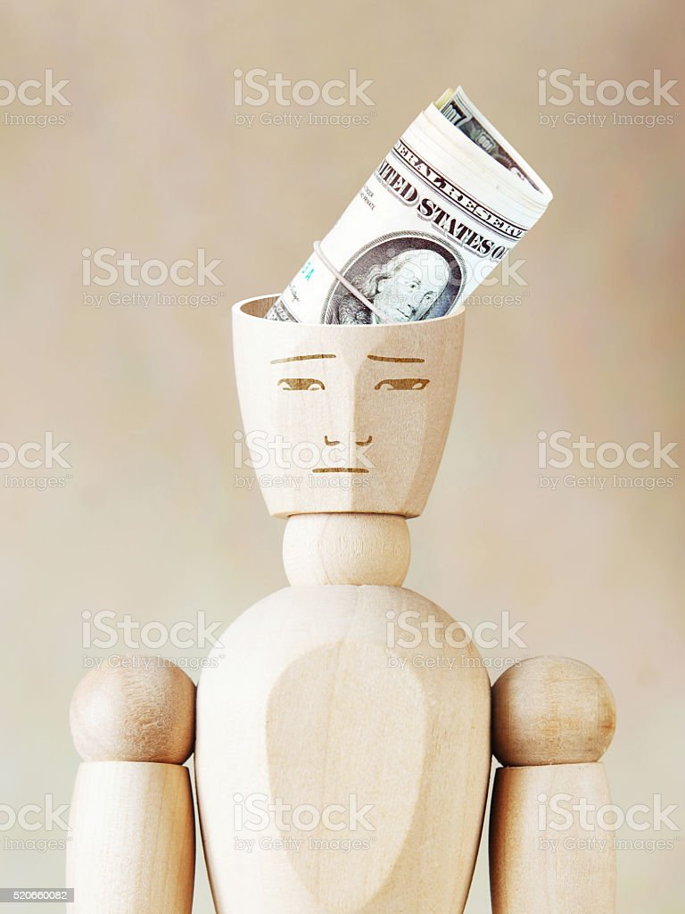 Bundle of dollars into the human head stock photo