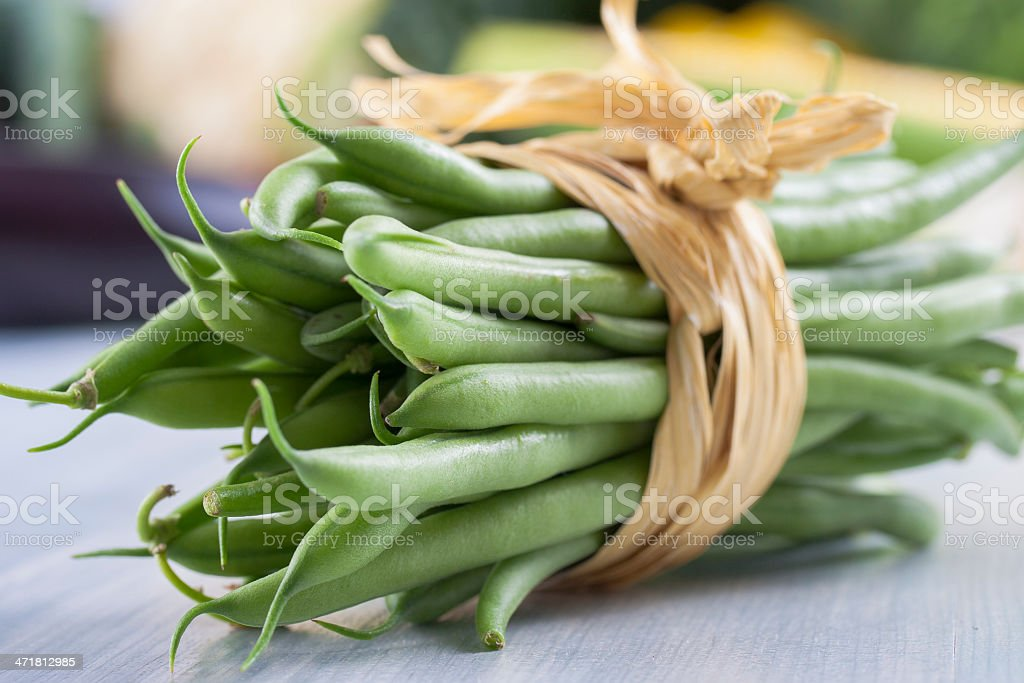 Bundle of fresh green beans tied with straw stock photo