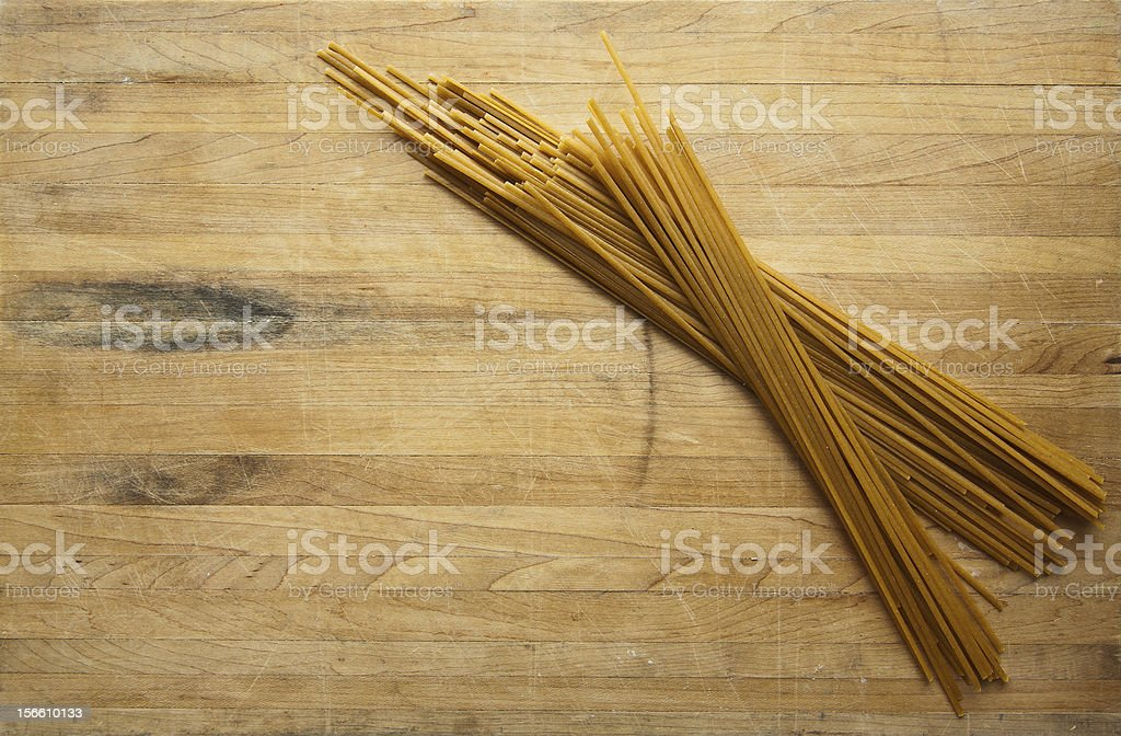 Bundle of Uncooked Spaghetti on Cutting Board royalty-free stock photo