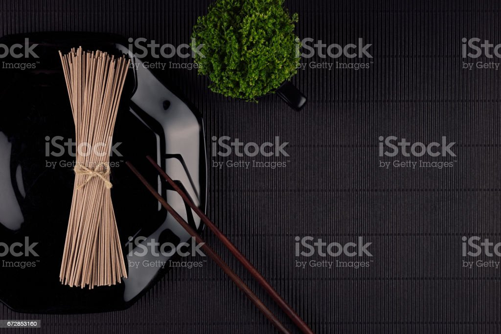 Bundle raw asian noodles in plate with chopsticks, green plant on black striped mat background with copy space, top view. Modern minimalistick style restaurant menu mock up. stock photo