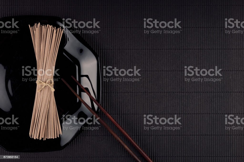 Bundle raw asian noodles in plate with chopsticks on black striped mat background with copy space, top view. Restaurant menu mock up. stock photo