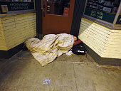 Bundled up homeless person sleep in door way of store