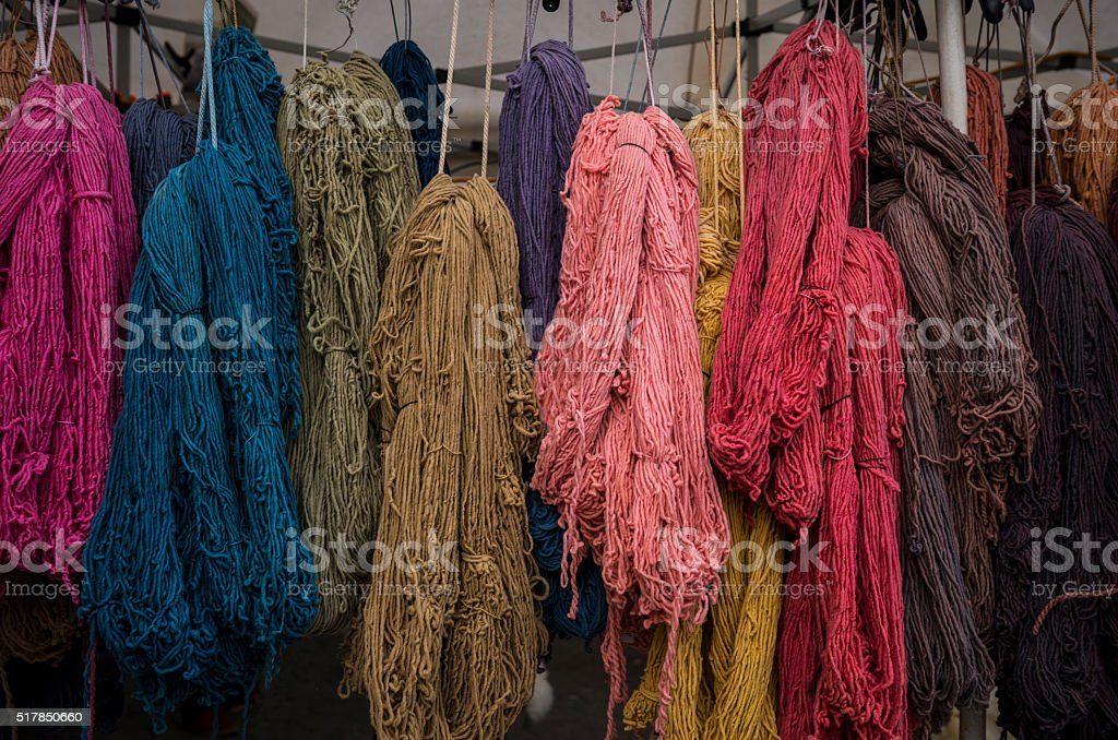 Bundles of colorful yarn hanging from ceiling in outdoor market stock photo